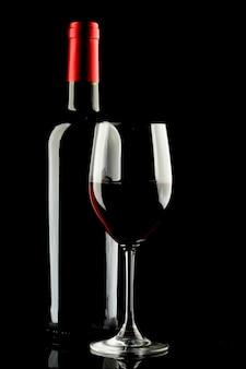 Verre de vin rouge et silhouette de bouteille sur fond noir