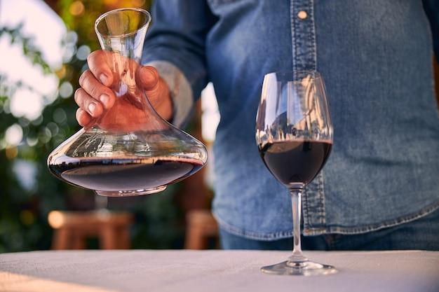 Verre de vin rouge sur la table. homme debout avec une carafe devant elle