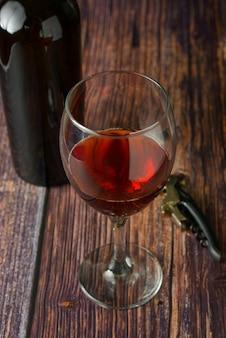 Verre de vin rouge sur une table texturée en bois rustique.