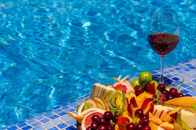 Un verre de vin avec des tranches de fruits se tient près de la piscine