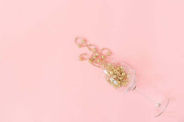Verre à vin versé boules de guirlande décoration de noël doré sur rose nouvel an, noël, concept de vacances