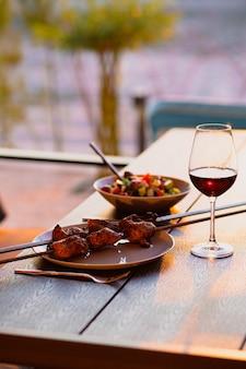 Un verre de vin avec de la viande grillée sur la terrasse d'étédîner dans la rue avec du vinméditerranée