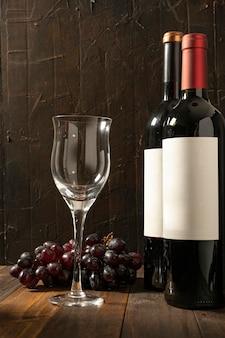 Verre à vin vide à côté de deux bouteilles de vin rouge sur une table en bois rustique et fond sombre. grappe de raisin derrière.