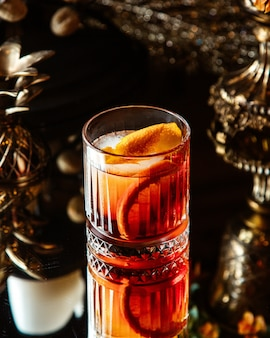 Un verre à viski avec cocktail d'orange et zeste d'oranges