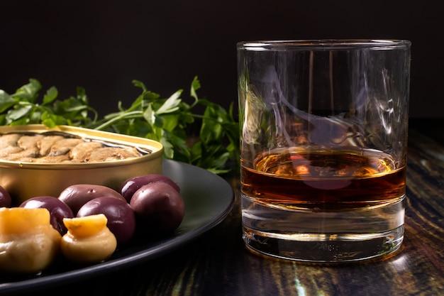 Un verre de whisky et un apéritif d'élite sur fond noir.