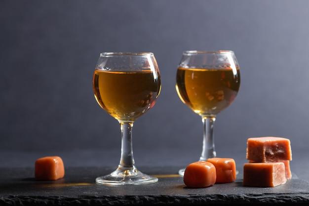 Verre de whisky avec des bonbons au caramel sur une ardoise en pierre noire. vue de côté