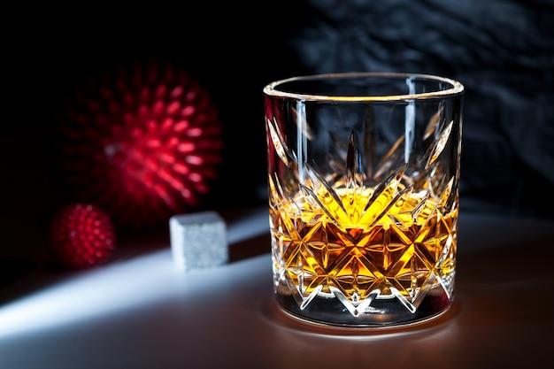 Verre de whisky ou de brandy sur fond sombre à côté d'un modèle abstrait de souche virale. ivresse.