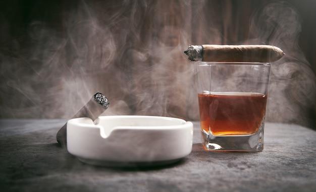 Verre de whisky, cendrier et cigares sur la table