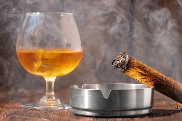 Verre de whisky et cigare allumé dans un cendrier