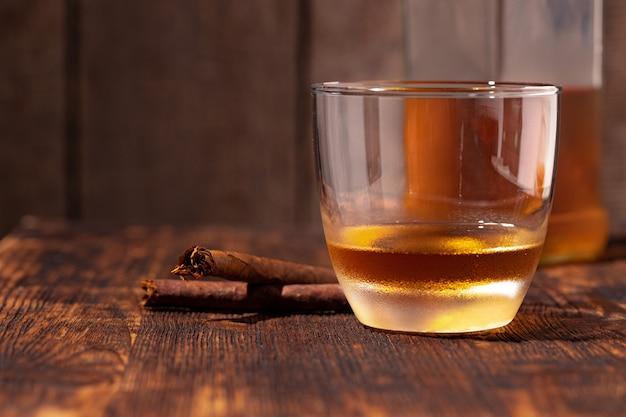 Un verre de whisky et de cigare sur une table en bois se bouchent