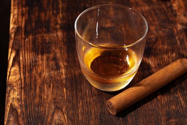 Un verre de whisky et de cigare sur une table en bois