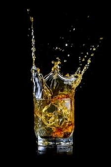 Verre de whisky éclaboussant ou autre alcool avec glaçon isolé