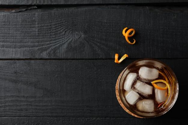 Verre de whisky et d'écorce d'orange sur bois