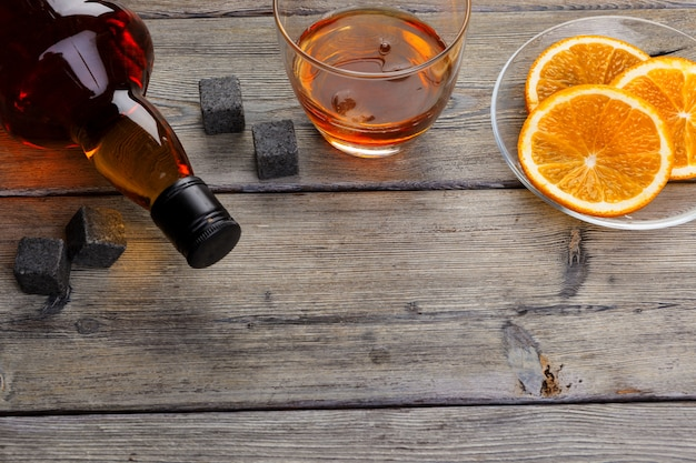 Verre à whisky avec fruits orange coupés sur une surface en bois foncée