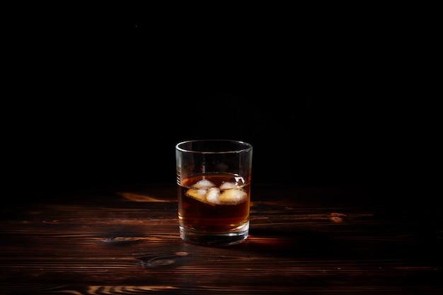 Verre de whisky avec de la fumée et de la glace sur une table en bois