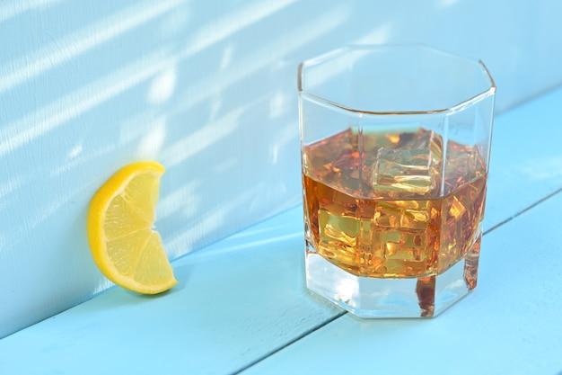 Verre de whisky avec de la glace et du citron sur un fond en bois rustique bleu.