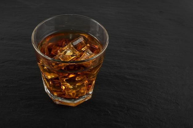 Verre de whisky glacé sur fond de pierre noire naturelle