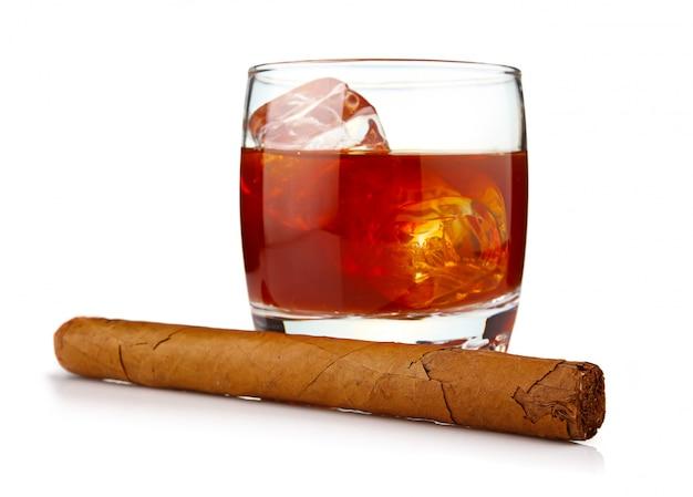 Verre de whisky avec des glaçons et cigare havane isolé