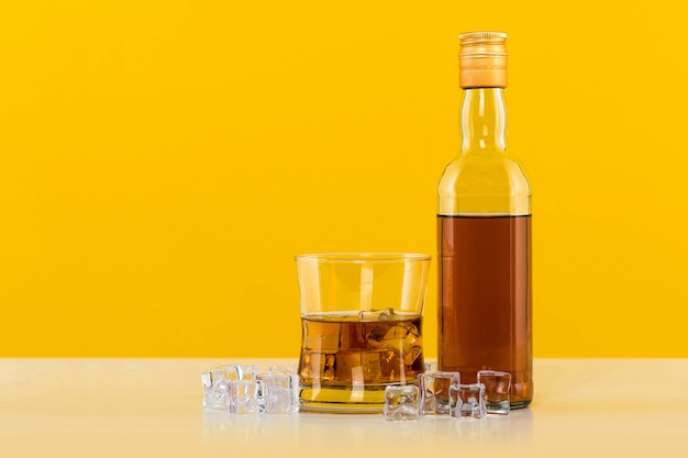 Verre de whisky avec des glaçons sur mur jaune
