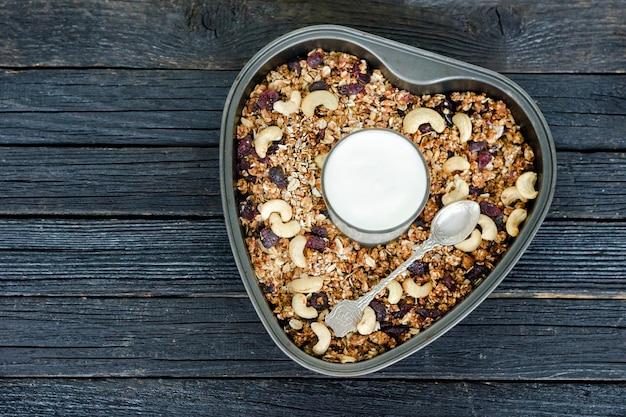 Verre de yaourt et granola aux noix de cajou dans une casserole. table en bois noir