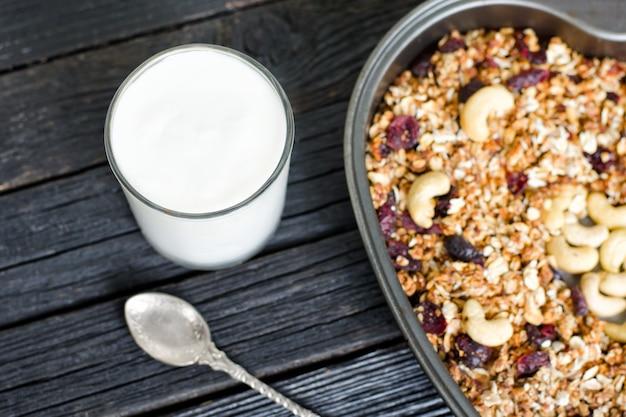 Verre de yaourt et granola aux noix de cajou sur une plaque à pâtisserie. table en bois noir