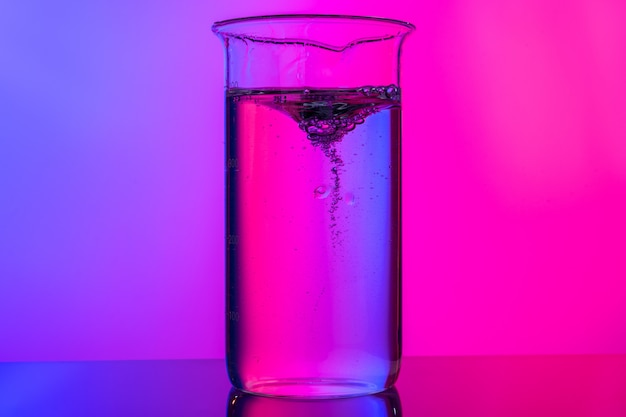 Verrerie chimique bouchent sur fond néon rose-violet