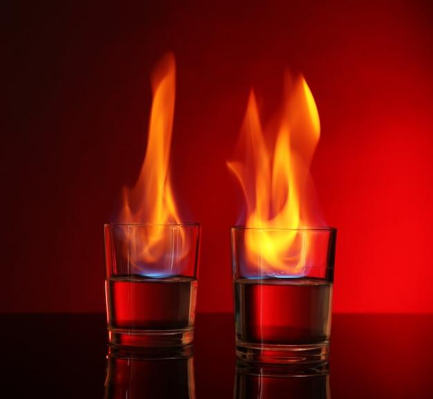 Verres avec de l'alcool brûlant sur fond rouge