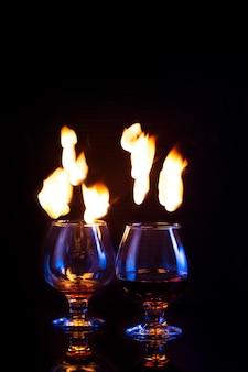 Verres avec alcool brûlant sur noir