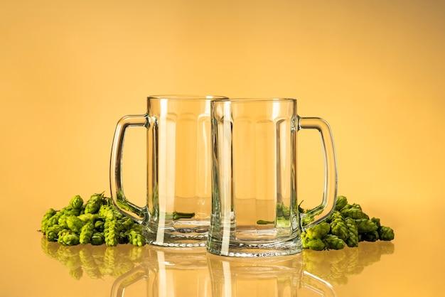Verres à bière avec du houblon sur un fond homogène
