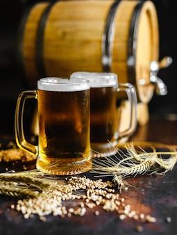 Verres à bière et épices de blé sur une vieille table en bois rustique sur fond noir