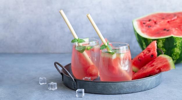 Verres de boisson d'été froide avec pastèque, glace, menthe. concept de boissons maison