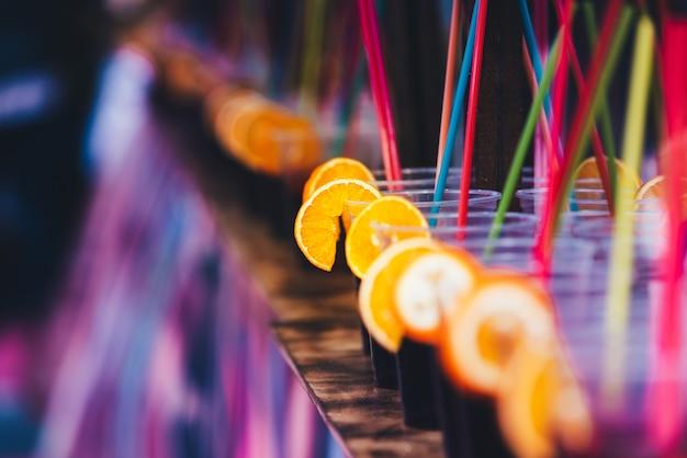 Verres avec des boissons alcoolisées et des tranches de fruits lors d'une fête de la jeunesse.