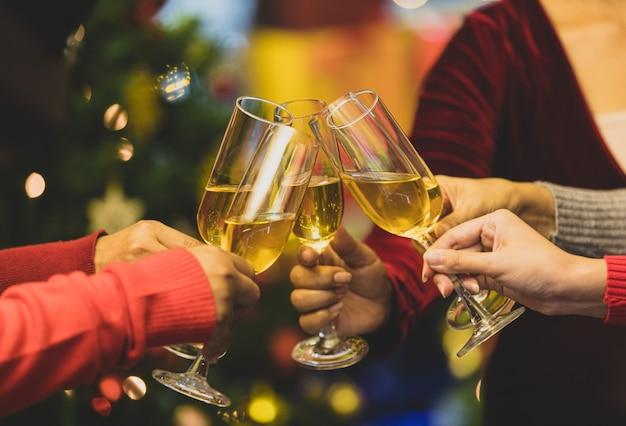 Verres à boissons trinquant moment par des amies joyeuses sur un pull, tout en profitant de la célébration d'une relation heureuse lors d'un délicieux événement de la soirée de noël. ajoutez du bruit pour s'adapter à l'image de style vintage.