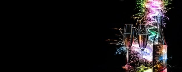Verres et bouteille de champagne dans des étincelles colorées de ligh du bengale