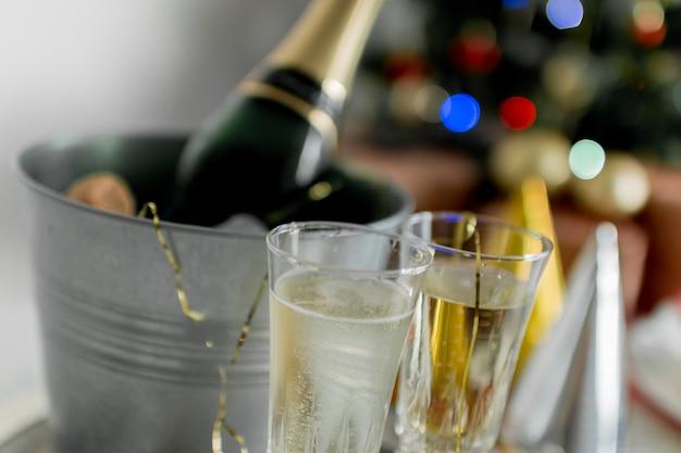 Verres et bouteille de champagne dans un récipient de glace