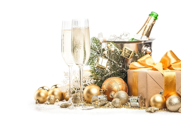 Verres et bouteille de champagne avec des décorations et des cadeaux de noël