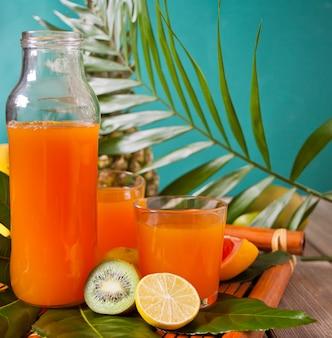 Verres et bouteille de jus multifruit exotique tropical avec ananas et feuille de palmier en arrière-plan