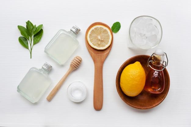 Verres et bouteille pour des boissons avec des tranches de citron, de la menthe et du miel.