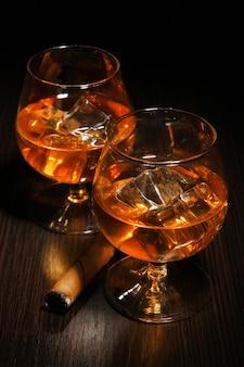 Verres à brandy avec de la glace sur fond de bois