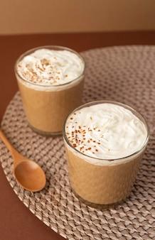 Verres à café avec crème fouettée sur table