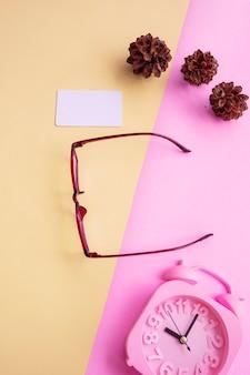 Verres carrés sur fond rose et jaune avec accessoires supplémentaires, réveil et fleurs de pin. style d'été minimal