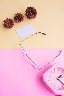 Verres carrés en métal sur la photo dans un style estival minimal sur fond rose pastel et jaune. réveil , fleurs de pin , cartes de visite