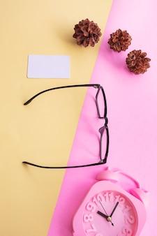 Verres carrés sur la photo dans un style estival minimal sur fond rose et jaune pastel. réveil , fleurs de pin , cartes de visite