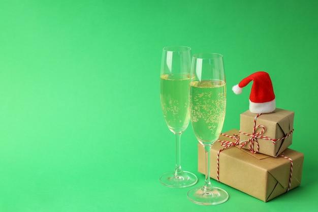 Verres de champagne, bonnet de noel et coffrets cadeaux sur fond vert.