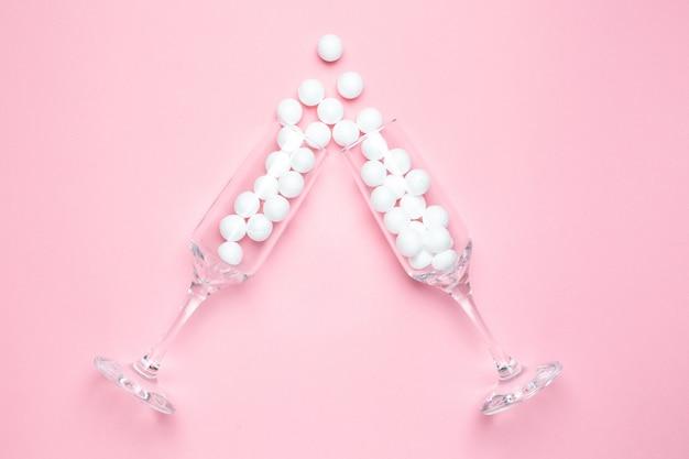 Verres de champagne avec des boules blanches sur le style minimal rose.
