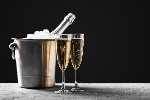 Verres de champagne avec une bouteille de champagne dans un seau