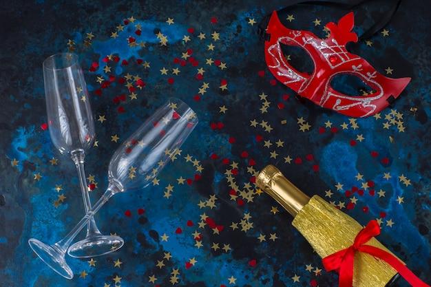 Verres de champagne, bouteille de champagne, masque et confettis