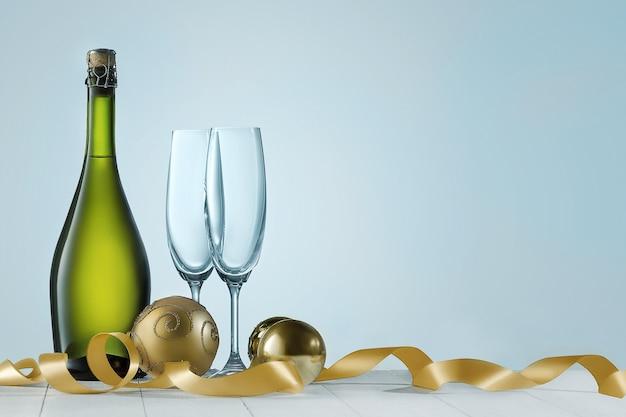 Verres à champagne et bouteille sur fond bleu mousseux de vacances