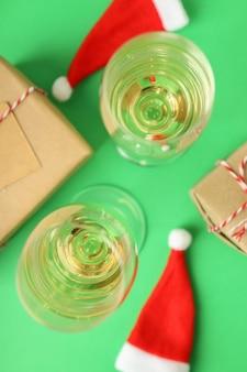 Verres de champagne, chapeaux de père noël et coffrets cadeaux sur fond vert.