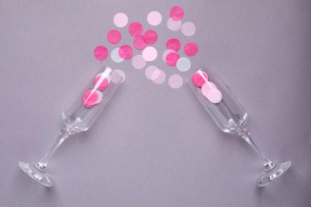 Verres de champagne avec des confettis roses sur un gris